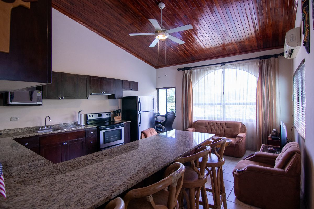2 of 10: Living room and kitchen with granite counter tops