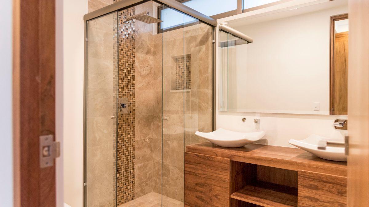 21 de 38: Baño principal con cancel y mueble con doble lavabo