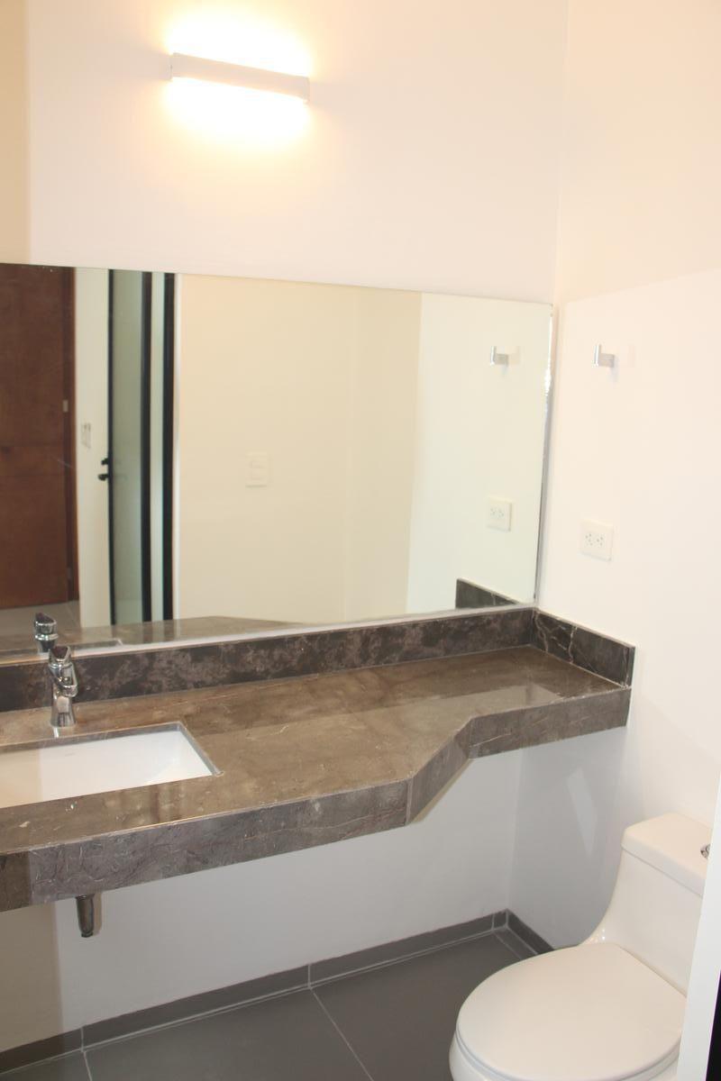 18 de 43: Baño en planta baja con espejo, mármol y accesorios.