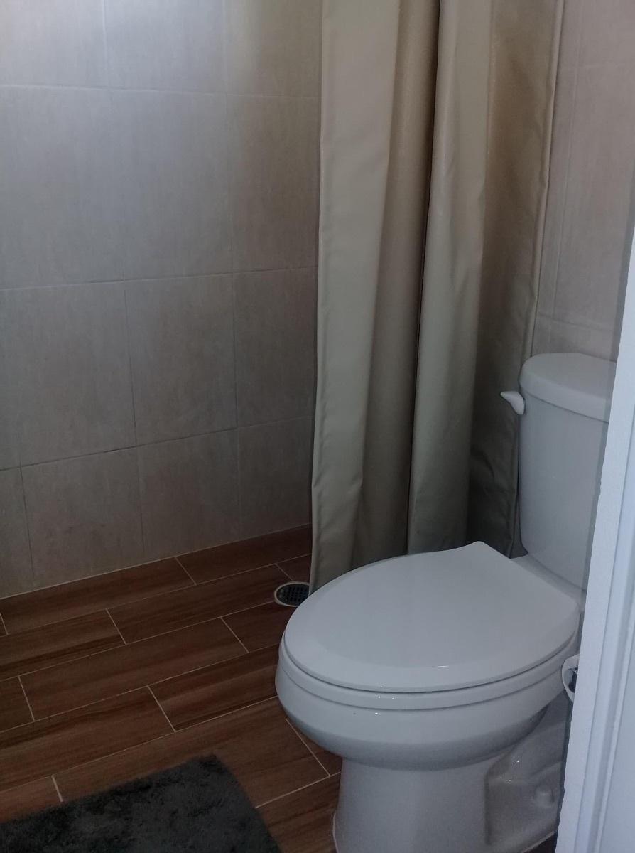 10 de 10: Baño y regadera forrado con loza y cortina.