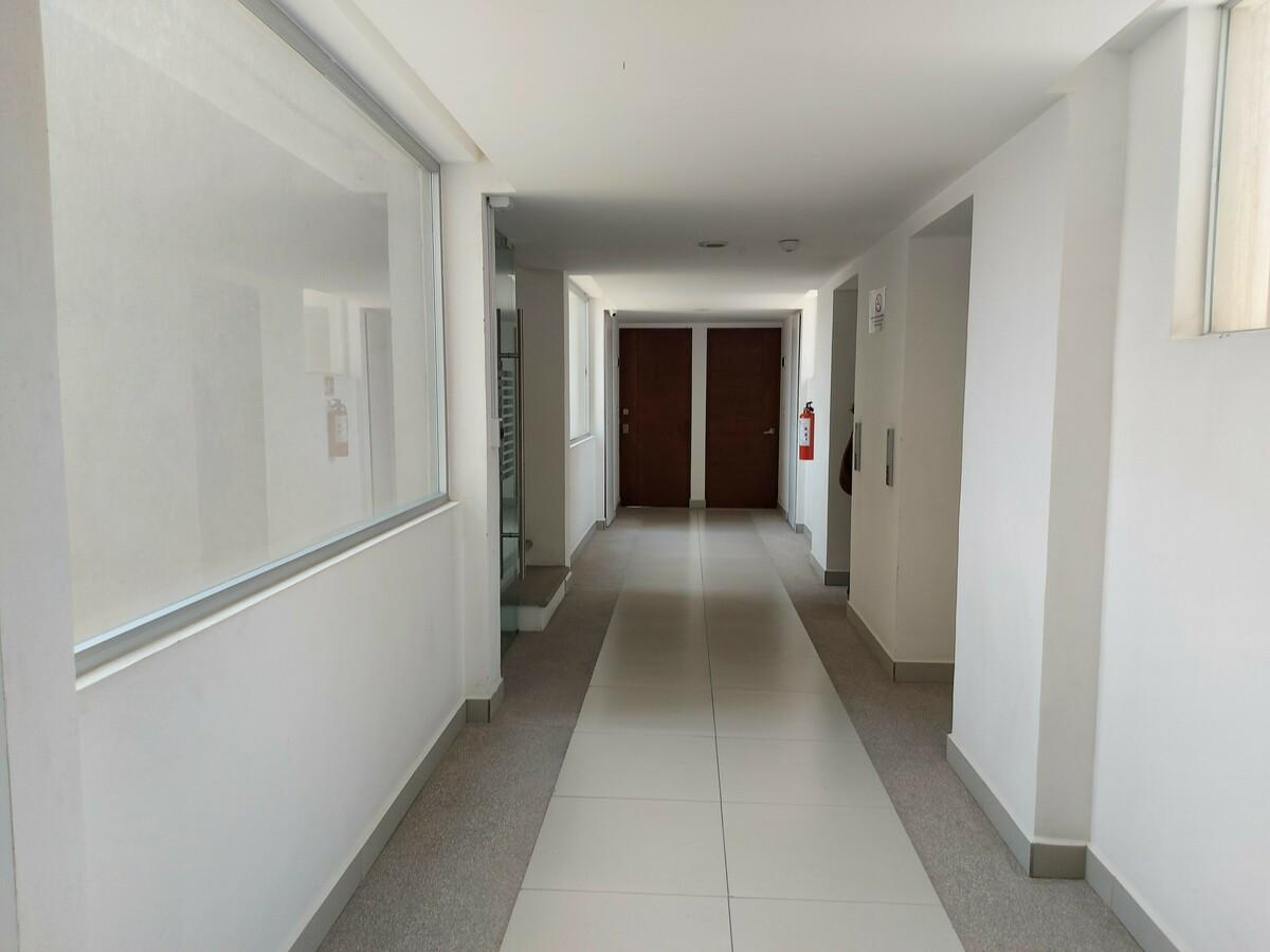5 de 20: Pasillo con elevador y puerta de seguridad en escaleras