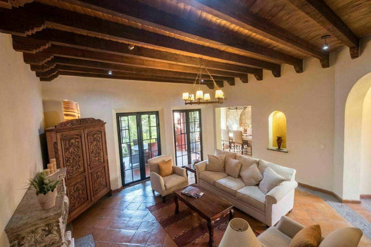 5 de 28:  Sala con chimenea y techo de tejamanil con vigas en madera.