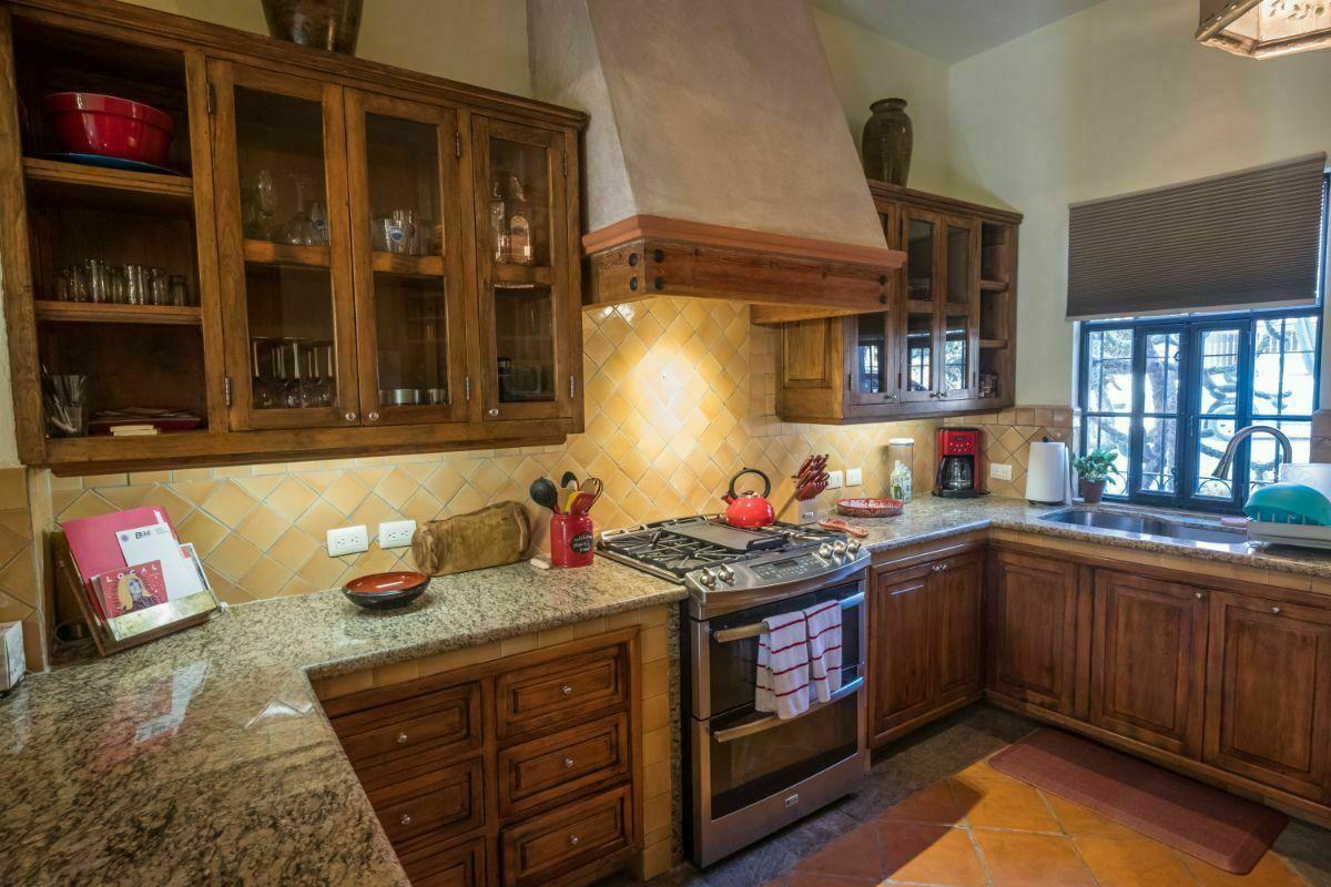 7 de 28: Cocina con barras de granito y cocina equipada.
